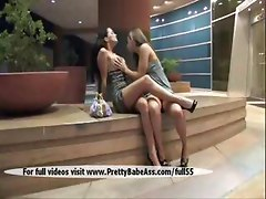 Two beautiful girls kissing in public